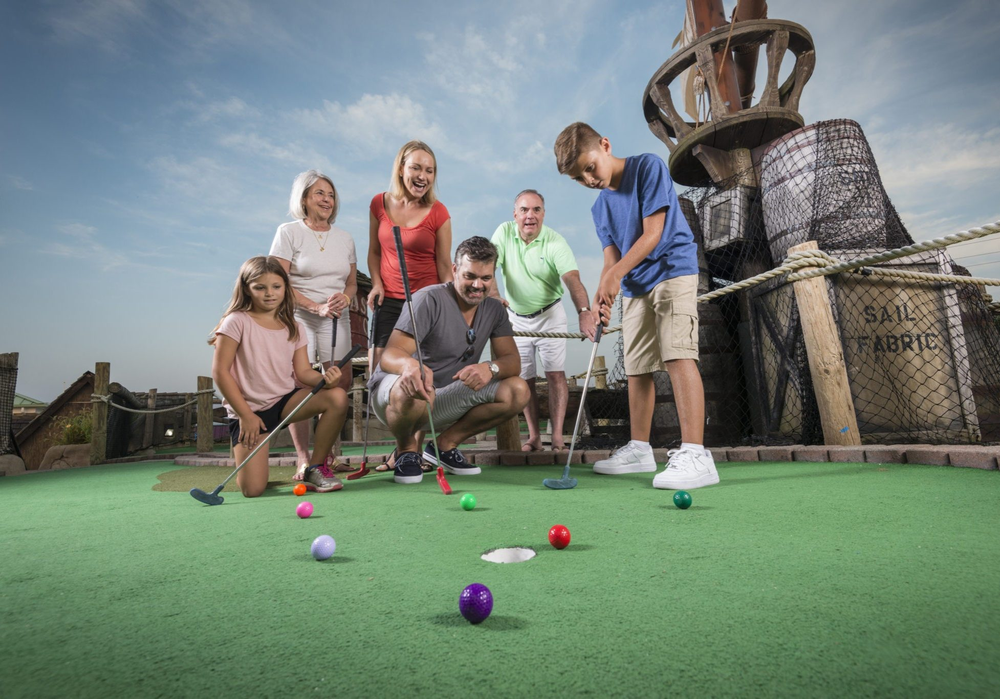 Photo of family playing mini golf